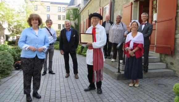 QAHN representative Sandra Stock (left) presented the 2021 Evans Award to a costumed Jim Kyle of the Château Ramezay English-speaking Guides Association at an informal ceremony in the museum's garden. ©Château Ramezay – Historic Site and Museum of Montréal.